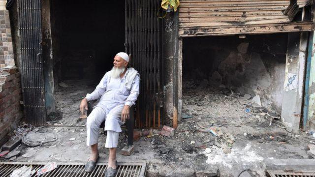 উত্তর-পূর্ব দিল্লিতে দাঙ্গায় পুড়ে ছাই হওয়া দোকানের সামনে বসে একজন ব্যবসায়ী