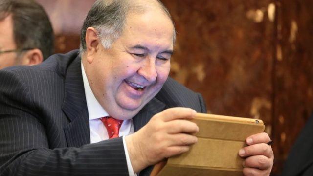 Алишер Усманов смеется, гляд в планшет