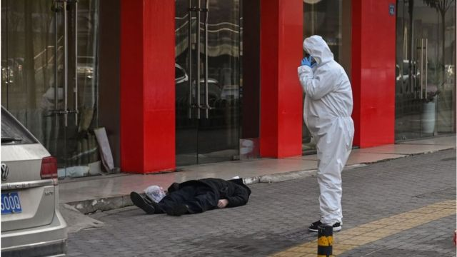 This photo taken on January 30, 2020 shows an official in a protective suit checking on an elderly man wearing a facemask who collapsed and died on a street near a hospital in Wuhan