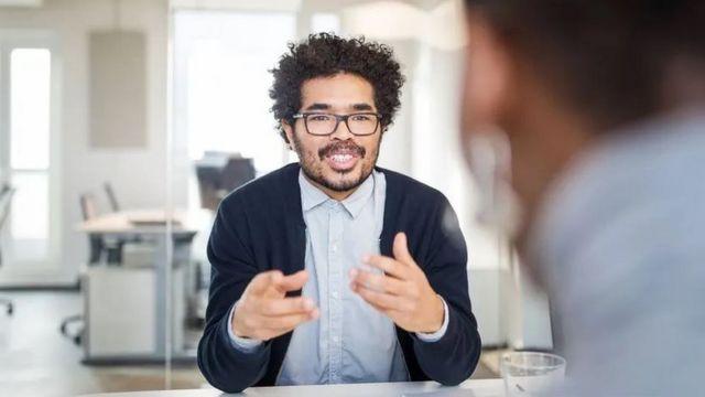Un hombre conversa con otro en una oficina