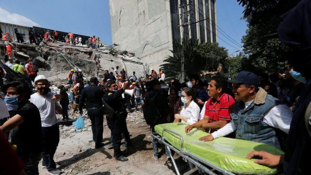 Equipos de rescate frente a un edificio derrumbado frente a un edificio que se mantuvo en pie en Ciudad de México.