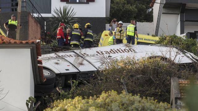 Equipes de emergência trabalham perto de ônibus caído em meio a casas