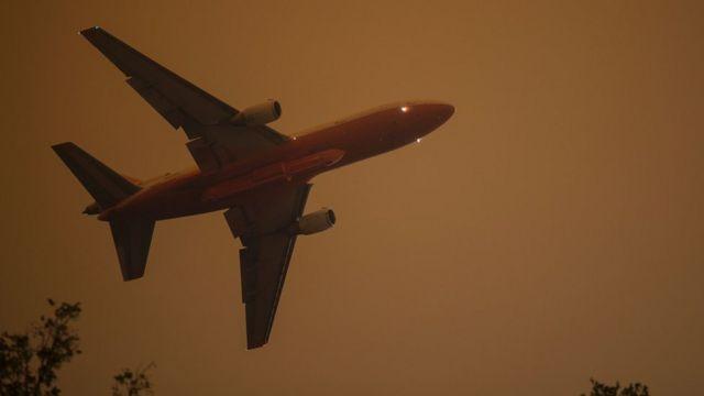 Un avión vuela contra un cielo ennegrecido.