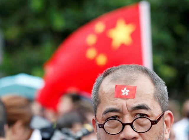 香港撑警集会现场,有群众手举中国国旗。