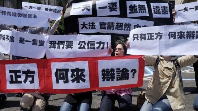 反對同婚人士3月24日憲法法庭開庭日在司法院外舉標語抗議。
