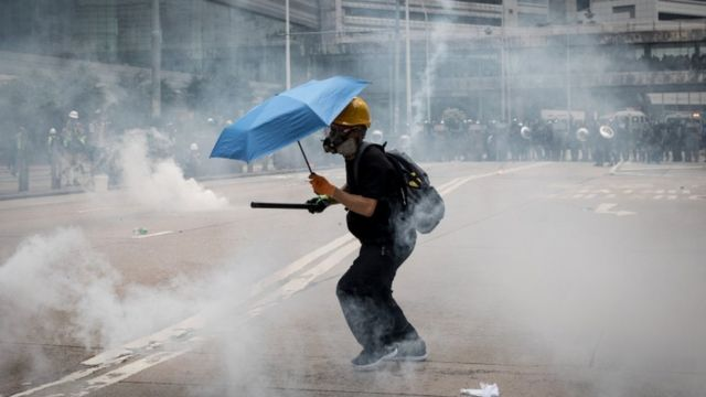 A lone protester wearing a gas mask and carrying an umbrella surrounded by tear gas in Hong Kong