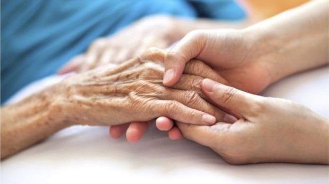 Mão de pessoa idosa junto a mão de pessoa jovem