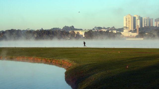 Una persona corriendo en la hierba, con vapor de agua sobre un charco en un escenario frío