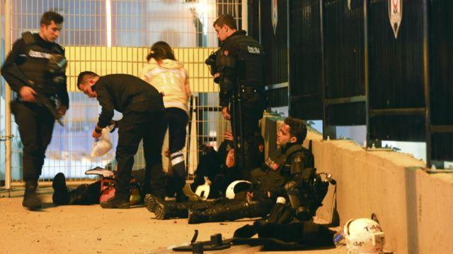 Para anggota kepolisian menolong rekan-rekan mereka yang terluka.