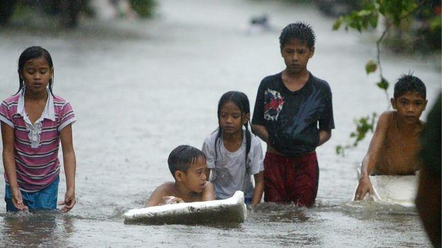 洪水の中を歩く子どもたち