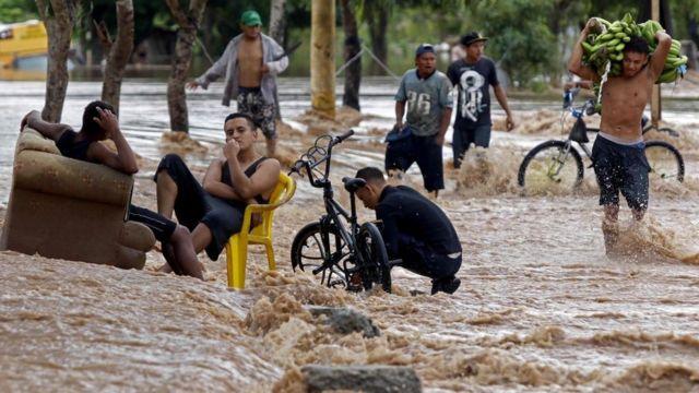 Personas en en medio una calle inundada