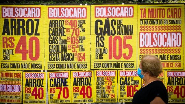 Idosa passa por cartazes da campanha 'Bolsocaro', que protesta contra a alta de preços no governo Bolsonaro