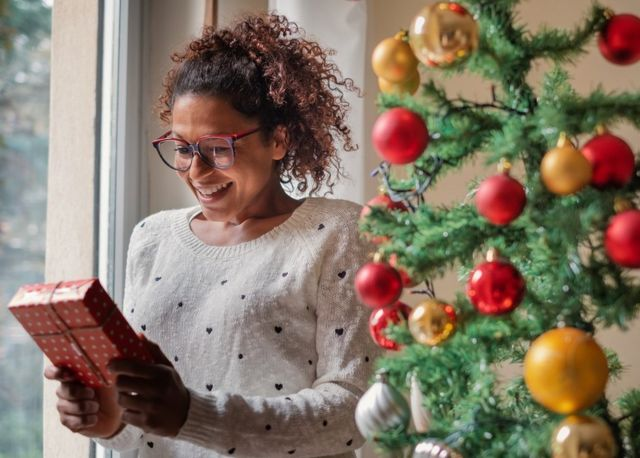 Happy woman standing next to a window and a Christmas tree, excited before opening her gift