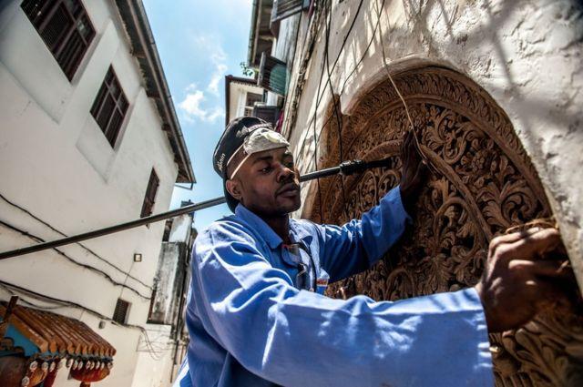 A traditional Zanzibari round-top door is repaired
