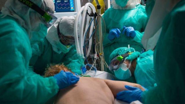 Equipe médica usando equipamentos de proteção individual coloca paciente de bruços em leito de uti