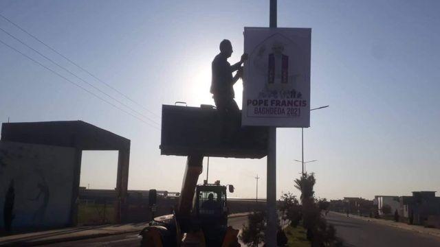 Homem pendura cartaz sobre checada do Papa Francisco