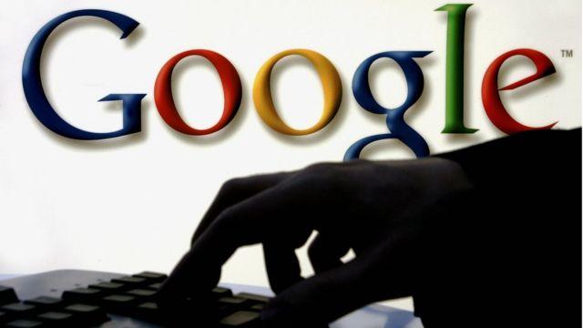 sombra de uma mão escrevendo em um teclado com o logotipo do Google atrás