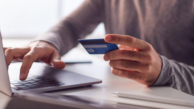 Homem na frente do computador com cartão de crédito