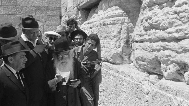 Un grupo de judíos rezan junto al Muro de los Lamentos.