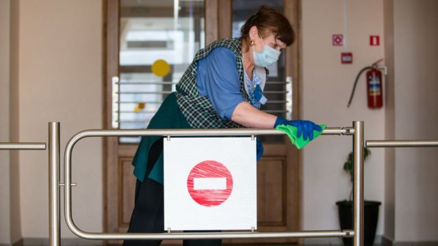 A cleaner sanitises a railing inside a school building