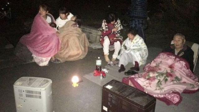 道路に避難し毛布とストーブで暖をとる人たち(15日)