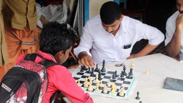 Un joven y un hombre jugando ajedrez