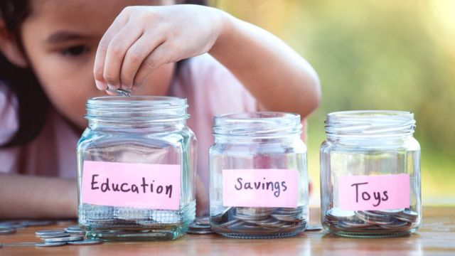 A child puts coins in different jars labelled education, savings and toys