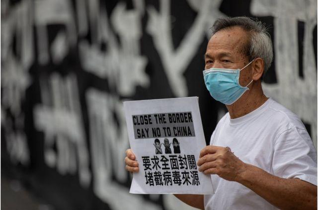 香港醫管局員工陣線成員在醫院管理局大樓外手持標語牌舉行罷工(資料照片)。