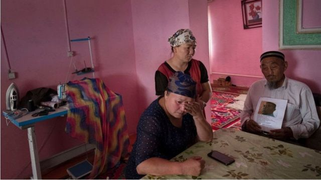 Gulzira Auelkhan, centre, at home in her village. She was forced to restrain women in the camps, she said