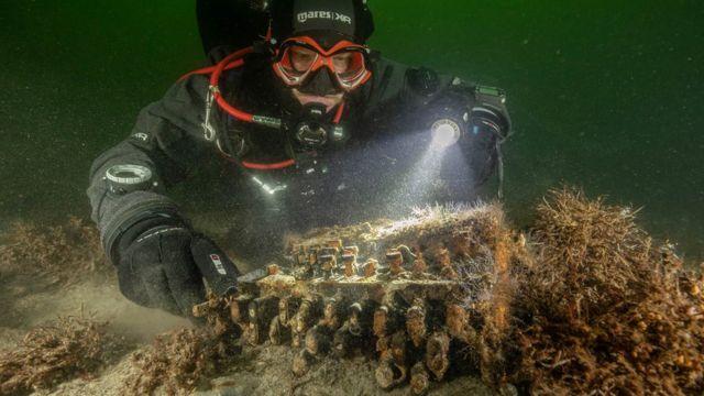 Un buzo junto a la máquina Enigma en el fondo del mar.