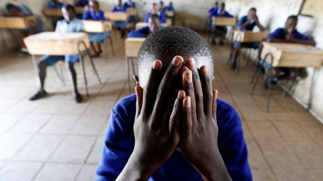 A student dey pray inside classroom before im primary school final national examination for Kiboro Primary school, Nairobi, Kenya - 31 October 2017