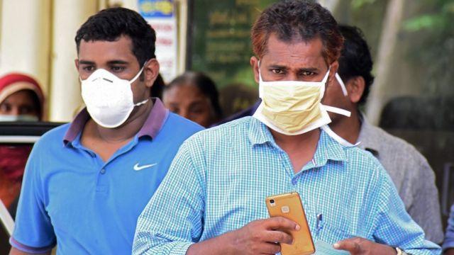 Dos hombres indios con máscaras cubrebocas.