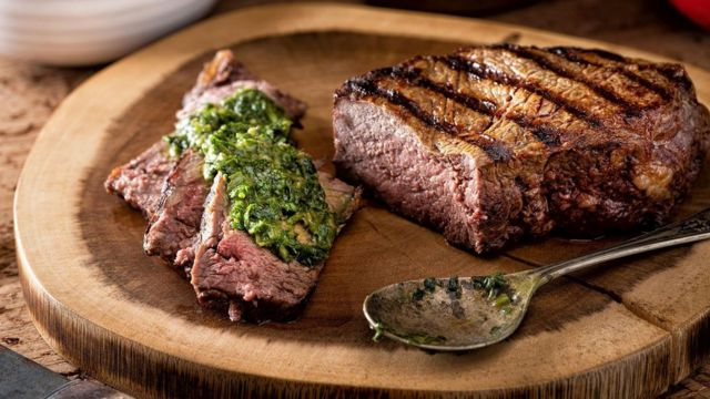 Plate of roast beef with chimichurri.