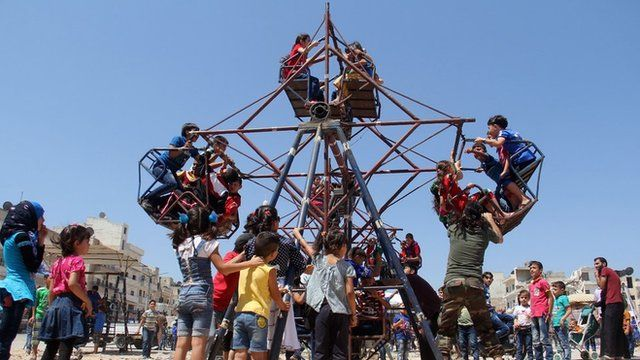 Children ride on an fairground attraction as they celebrate Eid al-Fitr in Syria's rebel-held north-western city of Idlib.