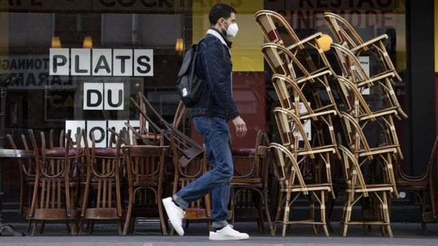 Homem caminha em frente a café fechado com as cadeiras empilhadas em Paris