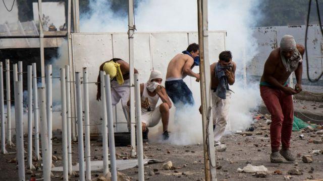 Manifestantes protegiéndose de los gases
