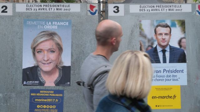 Dos personas pasan junto a dos carteles con propaganda de Le Pen y Macron.