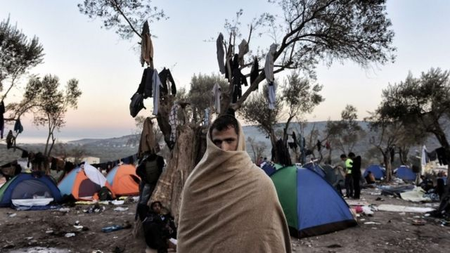 A man with a blanket wrapped around his head and shoulders stands near tents where refugees and migrants live in a field outside the Moria registration center on the Greek island of Lesbos on November 11, 2015