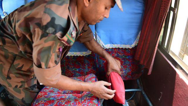 観光バスの座席の下に隠された違法薬物を押収するバングラデシュの治安担当者