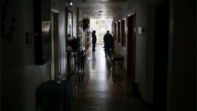 People in a corridor of a building without light