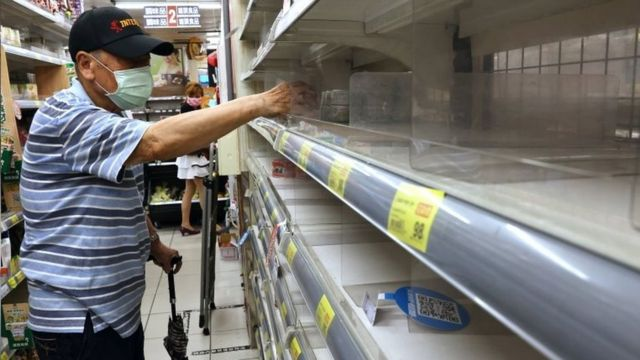 A man takes instant noodles from a near-empty shelf in a supermarket in Taipei, Taiwan. Photo: 16 May 2021