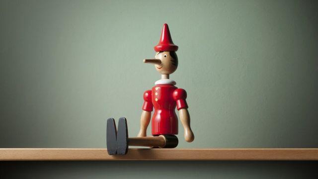 A wooden Pinocchio figurine, sitting on a shelf