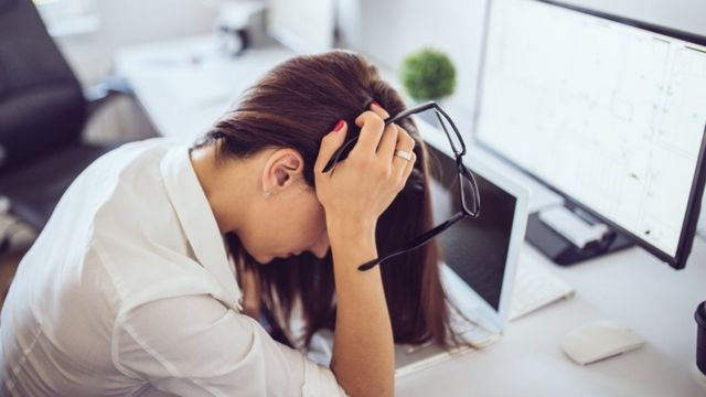 Una mujer se toca la cabeza porque está cansada en el trabajo.