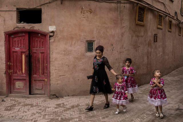 Sincan'da, Kaşgar'ın eski şehir bölgesinde çocularıyla yürüyen bir kadın.