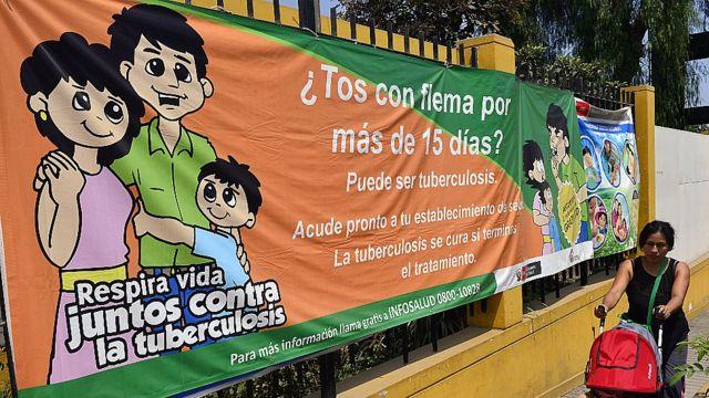 Mujer con su niño en Perú pasando frente a una pancarta que insta a la gente a acudir al médico si han tenido tos con flema por más de 15 días.