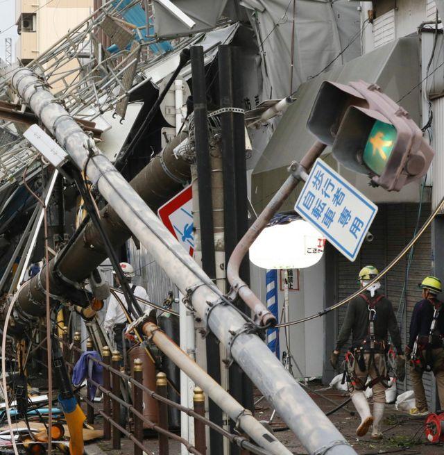 Porušeni stubovi na ulici i radnici sa šlemovima