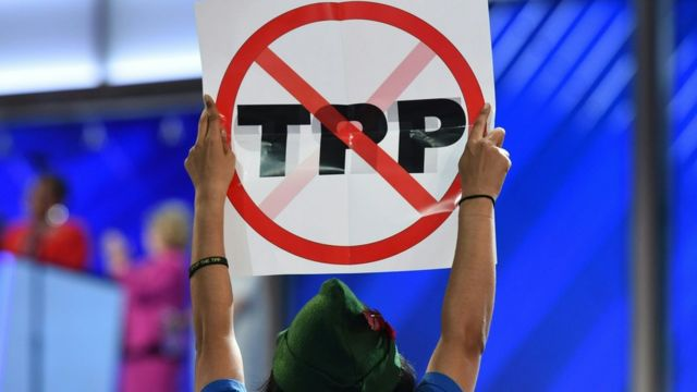 """Mujer con cartel que dice """"TPP"""" tachado."""