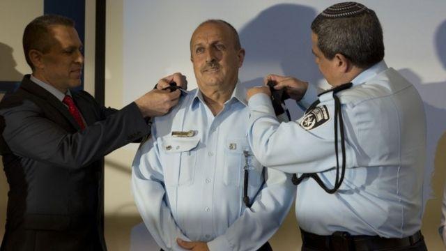 昇進式に臨むハクルシュさん(写真中央/13日、イスラエル・テルアビブ)