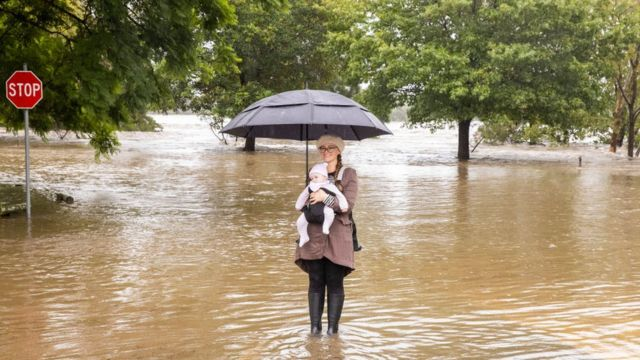 Perempuan dan seorang bayi berfoto saat banjir.