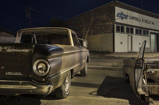 مركز لصيانة السيارات أمامه سيارة قديمة
